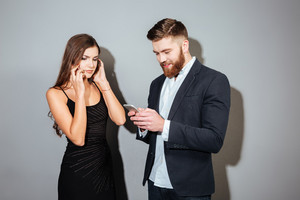 Two young businesspeople in smart clothes using mobile phones over gray background