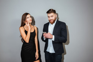 Two young businesspeople in smart wear holding mobile phones over gray background