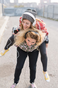 Two young curly and straight blonde hair caucasian woman listening music with headphones, one holding the other on piggyback ride - music, having fun, friendship concept