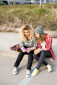 Two young curly and straight blonde hair caucasian woman sitting on a sidewalk the city, using a smartphone, looking downward the screen - technology, social network, communication concept