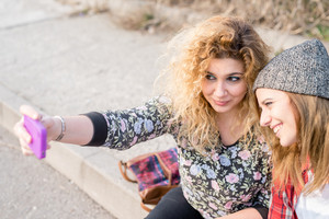 Two young curly and straight blonde hair caucasian woman sitting on a sidewalk, using a smartphone, taking a selfie - technology, social network, communication concept