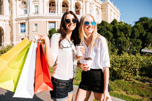 Two young fashion women with shopping bags having fun outdoors