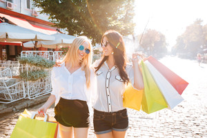 Two young fashion women with shopping bags walking along the street