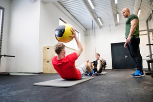 Two young fit men in crossfit gym with their personal trainer exercising with medicine balls, doing crunches.