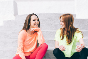 Two young friends in sportswear talking and laughing outdoors, close-up