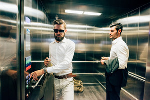 Two young handsome black and blonde hair bearded modern businessman in a elevator, one holding a bag and wearing sunglassesn- business, working, successful concept