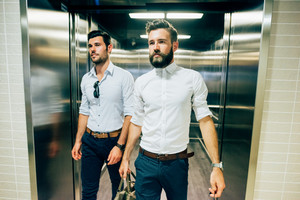Two young handsome black and blonde hair modern businessman exiting from a elevator, one holding a bag, both overlooking right - business, working, successful concept