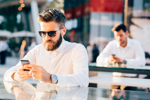 Two young handsome black and blonde hair modern businessman, sitting on a counter, using a smartphone, looking downward the screen - work, business, technology concept