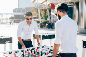 Two young handsome blonde and black hair caucasian modern businessman playing table football - break, having fun, competition concept
