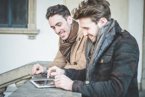 two young handsome businessmen using tablet  outdoors