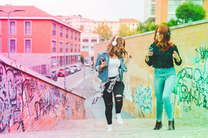 Two young handsome caucasian blonde and redhead straight hair women dancing in the city listening music with headphones and smartphone, laughing - music, fun, freedom concept - colorful filtered