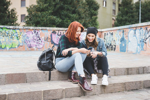 Two young handsome caucasian blonde and redhead straight hair women sitting on a staircase using a smartphone, looking downward the screen - social network, technology, communication concept