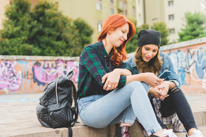 Two young handsome caucasian blonde and redhead straight hair women sitting on a staircase using smartphone, looking downward the screen - social network, technology, communication concept - side view