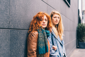 Two young handsome caucasian blonde and redhead woman friends posing outdoor in the city - friendship, interaction concept