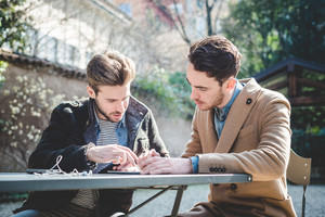 two young handsome fashion model businessmen using tablet  outdoors