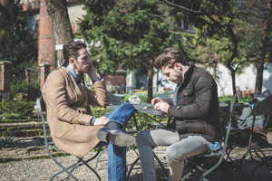 two young handsome fashion model using tablet man outdoors