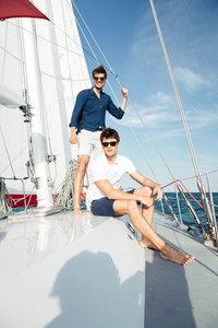 Two young handsome happy men friends standing on the yacht