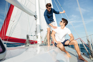 Two young handsome happy men talking while standing on the yacht