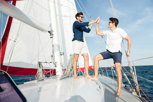 Two young handsome men greeting each other while standing on the yacht