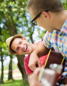 Two young happy men with guitar having fun outdoor
