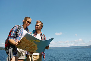 Two young hikers with backpacks looking at guide
