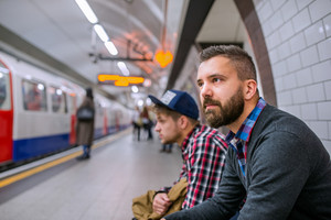 Two young hipster men sitting at the underground platform waiting