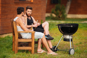 Two young men talking while preparing barbecue grill in park zone