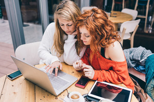 Two young millennials blonde and redhead woman using technological devices like computer, tablet and smart phone sitting at table in a bar - studying, technology, multitasking concept