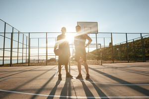 Two young sportsmen standing with basketball at the playgroung in the morning sun