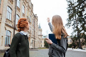 Two young teenage students standing outside university campus