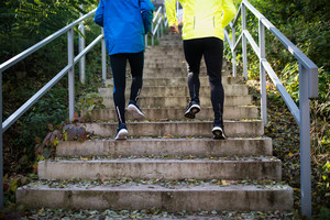 Two young unrecognizable athletes running on stairs outside in sunny autumn nature. Trail runners training for cross country race. Rear view.