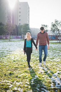 Two young woman of man couple walking outdoor in city back light hand in hand, smiling - love, relationship, happiness concept