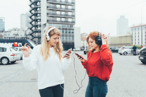 Two young women dancing listening music with smart phone outdoor - music, dancing, having fun concept