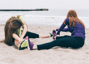 Two young women in sportswear doing stretching on the beach, concept of a healthy lifestyle