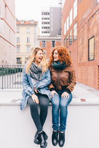 Two young women sitting outdoor in the city, blonde and redhead having fun - friendship, relaxing, having fun concept