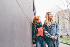 Two young women strolling outdoor in the city, blonde and redhead having fun - friendship, relaxing, having fun concept