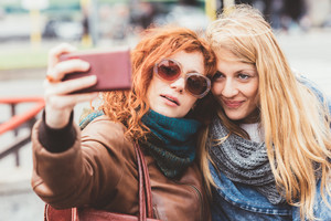 Two young women taking selfie with smart phone hand hold - sharing, technology, social network concept