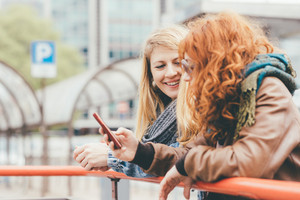 Two young women using smart phone outdoor  - technology, social network, communication concept