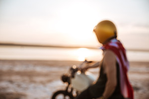 Unfocused image of man in american flag cape and helmet sitting on motorcycle