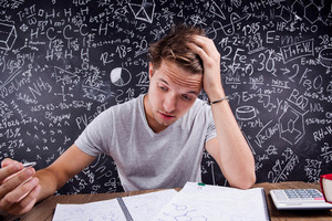 Unhappy hipster student doing his homework in front of a big blackboard