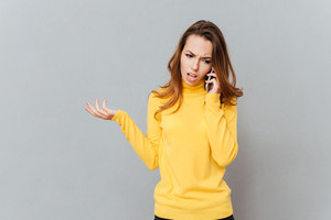 Unhappy stressed woman talking on mobile phone isolated on a grey background