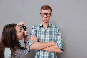 Unhappy young man in eyeglasses standing with arms folded while being photographed by a woman and looking at camera isolated on the gray background