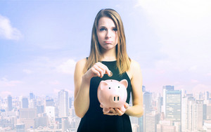 Unhappy young woman depositing money into her pink piggy bank