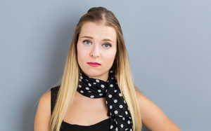 Unhappy young woman in front of a gray background