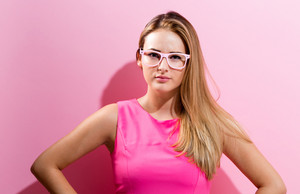 Unhappy young woman on a pink background