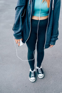 unrecognisable young woman with smart phone hand hold wearing tracksuit - sport, music, technology concept