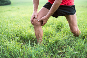 Unrecognizable active senior runner outside in field. Man with injured knee. Close up. Green sunny summer nature.