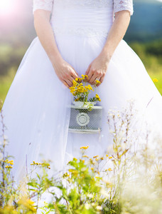 Unrecognizable beautiful young bride outside on a summer meadow at the sunset