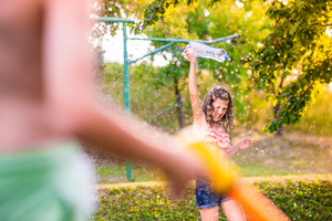 Unrecognizable boy splashing girl with water gun, fun in garden, sunny summer day, back yard