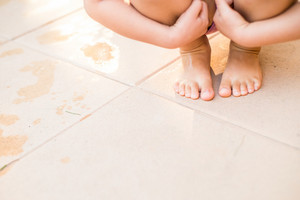 Unrecognizable child in swimsuit crouching on pavement, holding her knees, wet footprints, copy space